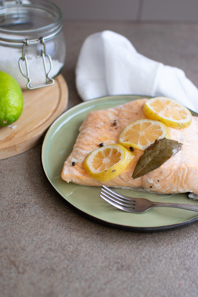 Salmon Topped with lemon slices on green plate